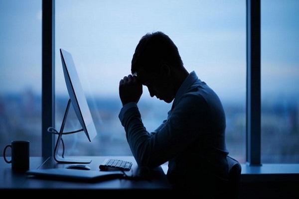 شاب يجلس حزينا ومتعبا على مكتبه أمام الكومبيوتر