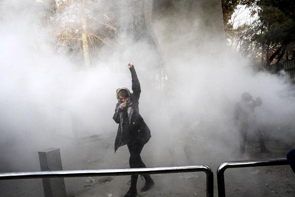سيدة تقف في مرمى قنابل الغاز في احتجاجات إيران 2017-2018