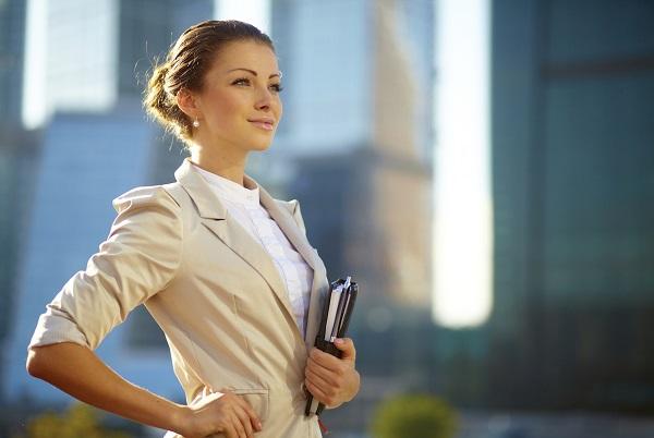 امرأة تقف وتنظر للأمام وتمسك كتب ومذكرا بيدها