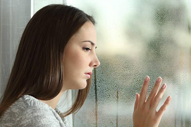 فتاة حزينة تقف أمام النافذة