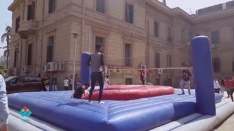 طلاب بجامعة القاهرة يلعبون كرة الطائرة أمام القبة